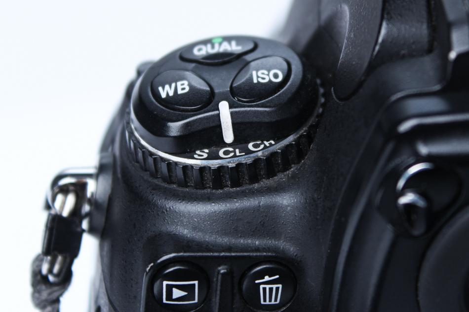 Włącznik trybu zdjęć seryjnych na obudowie Nikona D700. W niektórych aparatach opcja to może być dostępna tylko w elektronicznym menu.