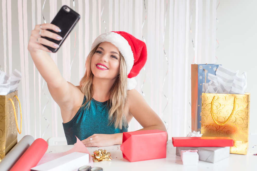 Pretty girl in Christmas hat taking selfies